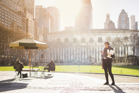 Woman waiting at Bryant Park against New York Public Library on sunny day