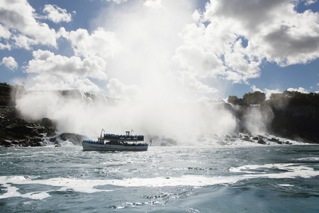 Ferry sailing by Niagara Falls against cloudy sky
