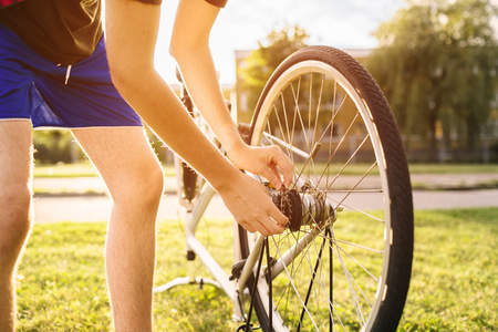 Midsection of sporty man repairing bicycle tire at park
