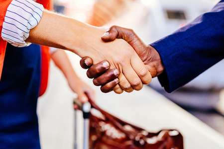 Cropped image of businesspeople shaking hands at railroad station LANG_EVOIMAGES