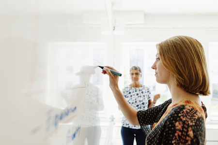 Lehrer, der Schreiben des weiblichen Kursteilnehmers auf whiteboard im Klassenzimmer aufpasst
