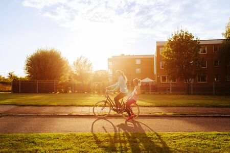 mode made: Side view of sporty women riding bicycle on street during sunset LANG_EVOIMAGES