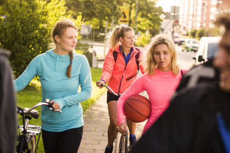 mode made: Basketball players walking with bicycles on sidewalk at park