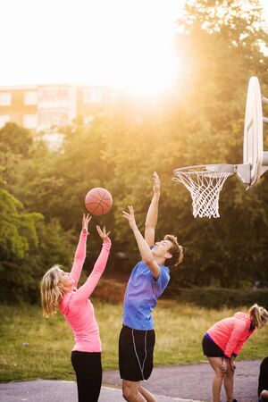 Man and woman playing basketball at park during sunset