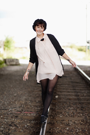 Portrait of young woman walking on railroad track