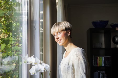 Happy young woman standing by window at home