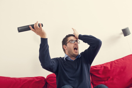 Surprised man holding remote control watching TV at home