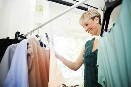 coathangers: Happy young woman selecting clothes from wardrobe at home LANG_EVOIMAGES