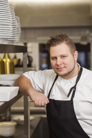 beings: Portrait of young male chef in kitchen LANG_EVOIMAGES