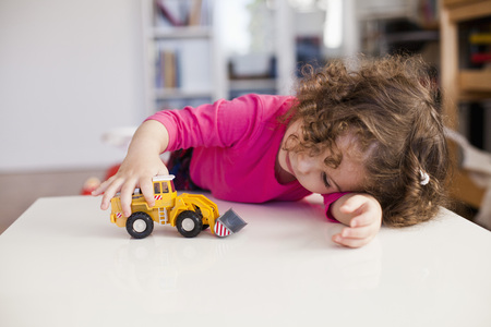 Baby girl playing with toy earth mover at home LANG_EVOIMAGES