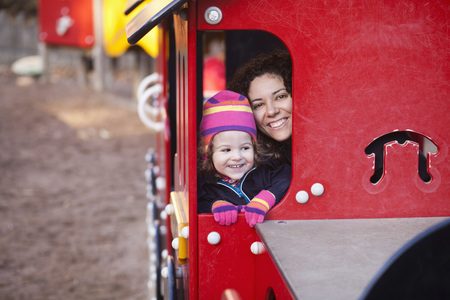 Portrait of happy woman with baby girl sitting in toy vehicle at park