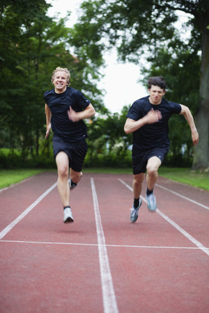 verticals: Two young men running on race track