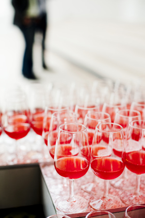 verticals: Large group of red wine glasses arranged on table LANG_EVOIMAGES