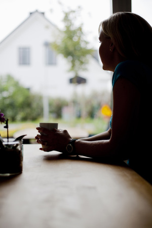 Mid adult woman with coffee cup sitting at table