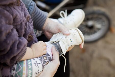 beings: Close-up of mothers hand putting shoe on baby girls foot