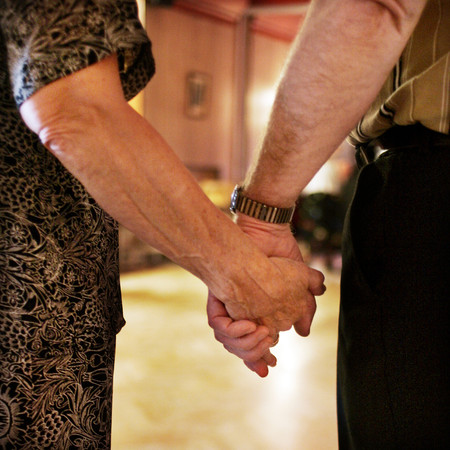 Two pensioners holding each others hands