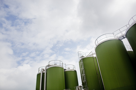 Low angle view of green silos against cloudy sky