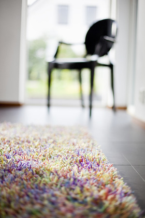 floor covering: Selective focus of area rug with chair in background