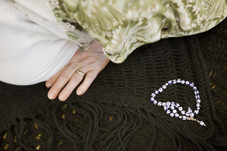 Cropped image of woman praying by beads in mosque