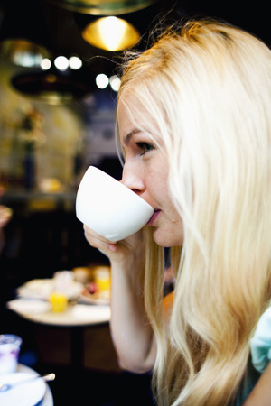 Woman drinking coffee at coffeehouse LANG_EVOIMAGES