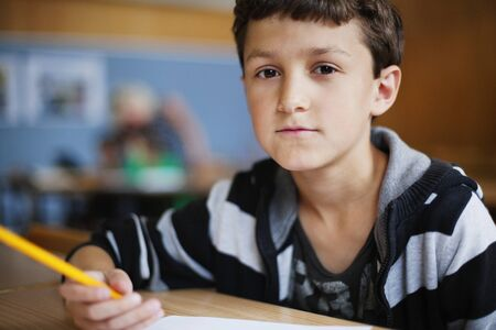 beings: Portrait of preadolescent boy sitting at desk in classroom