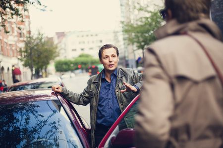 Mid adult man by car door talking to friend on road LANG_EVOIMAGES