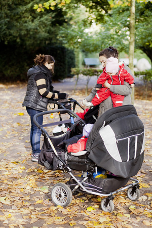 leafed: Female friends with their kids and baby carriages standing at park LANG_EVOIMAGES