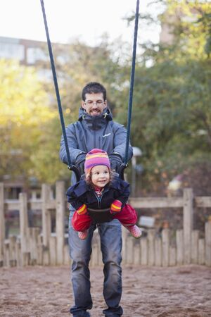 Happy father pushing his daughter on swing at park