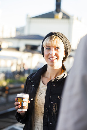 Happy young woman holding disposable cup looking at friend