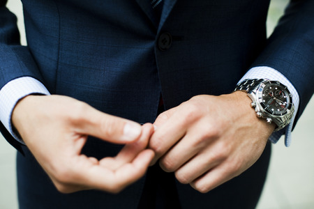 indecisive: Mid section of businessman in suit wearing wrist watch LANG_EVOIMAGES