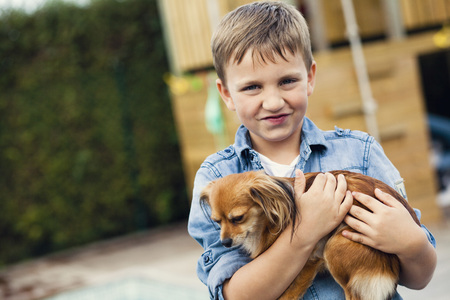 beings: Portrait of little boy holding puppy dog