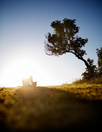 Mujer meditando bajo el árbol