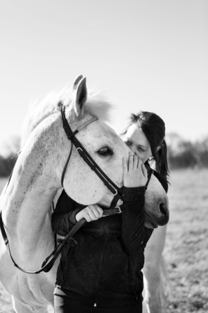 Woman kissing horse on sunny day LANG_EVOIMAGES