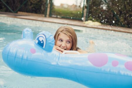 whimsy: Preadolescent girl playing in swimming pool