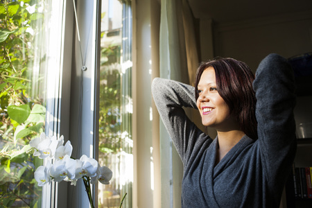 beings: Happy young woman looking out from window at home LANG_EVOIMAGES