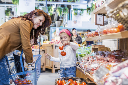 Girl holding tomatoes while standing by mother in supermarket