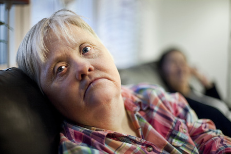Upset mature mentally challenged woman sitting on sofa in house LANG_EVOIMAGES