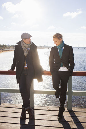 beings: Young gay couple standing on boardwalk by the ocean