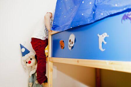 scaling ladder: Low section of preschooler boy climbing bunkbed in bedroom