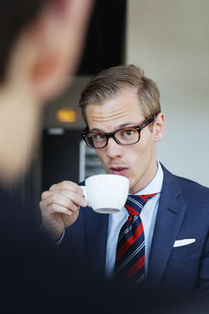 verticals: Portrait of young businessman holding coffee cup