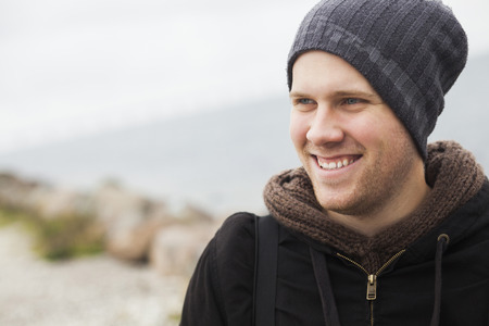 Young man wearing knit hat smiling LANG_EVOIMAGES