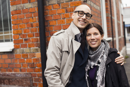 Portrait of couple smiling against brick wall LANG_EVOIMAGES