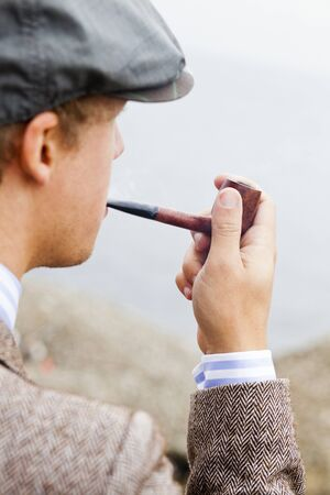 beings: Close-up of young man smoking pipe outdoors LANG_EVOIMAGES