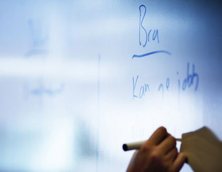Close-up of human hand writing on whiteboard