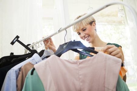 coathangers: Happy young woman selecting clothes from clothes rack at home