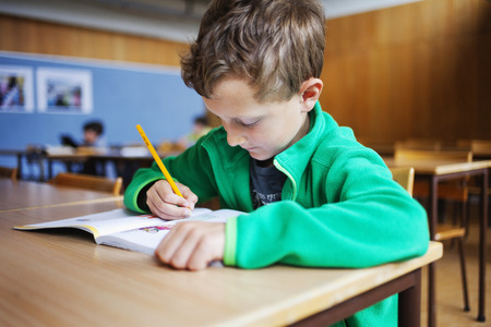 Schoolboy writing at desk in classroom