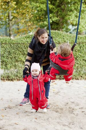 Happy mother with her twin daughters playing on swing at park