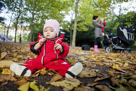 Portrait of baby girl in warm clothing sitting on ground with mother carrying twin sibling in the background LANG_EVOIMAGES