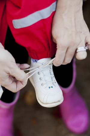 verticals: Close-up of mothers hand tying shoelace of baby girls shoe LANG_EVOIMAGES
