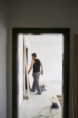 abodes: Man walking in construction site LANG_EVOIMAGES
